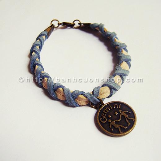 V01- Vòng tay cung hoàng đạo- 45k. Vòng tay được làm từ dây da lộn với kiểu tết cách điệu. Sự kết hợp giữa 2 màu trung tính xanh dương và nâu nhạt có thể phù hợp với cả nam và nữ. Điểm nhấn của chiếc vòng là mặt giả cổ cung hoàng đạo để thể hiện cá tính của chính bạn